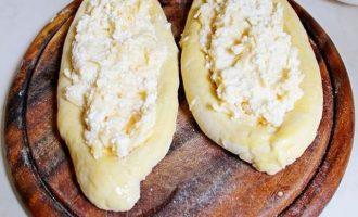 Духовой шкаф разогрейте до температуры 300 градусов, кондитерский противень застелите пекарской бумагой, смажьте слегка растительным маслом, выложите заготовки, заполненные по центру сырной начинкой.