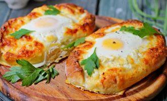 По прошествии указанного времени извлеките противень из духовки, выполните в сырной начинке отверстия, вылейте туда яйцо и продолжите еще выпекать 5-6 минут.