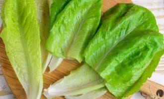 Вымойте и просушите листья салата ромэн. Оставьте мелкие листья нетронутыми; большие разрежьте пополам.