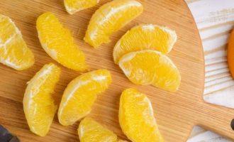 Очистите апельсин, удаляя как можно больше белой части и разделите на дольки.