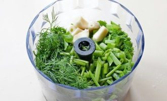 В рабочую камеру блендера выложите измельченную кинзу, укроп, петрушку и чеснок.