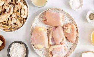 Вначале подготовьте все компоненты, которые идут в куриные бедра в грибном соусе. Для грибного соуса возьмите ароматные овощи: чеснок и петрушку, а также еще потребуются шампиньоны, сливки, куриный бульон и сухое белое вино типа - Шардоне.