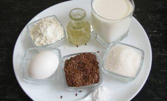 Для приготовления оладьей на кефире с семенами льна вначале подготовьте все компоненты: кефир любой жирности, пшеничную муку хорошего качества, которую заранее просейте, семена льна подсушите на сухой сковородке, а еще потребуется яйцо, соль, сахар и растительное масло.