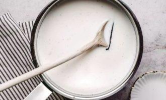 Влейте молоко и добавьте кусочки ванили или ванильный экстракт.