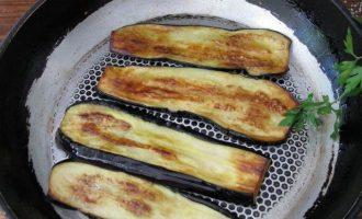 Сковородку хорошо разогрейте вместе с растительным маслом и поджарьте нарезанные баклажаны с двух сторон до красивого колера.