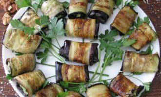 В завершение закуску в виде рулетиков из баклажанов с орехами поставьте в холодильник, а через 20 минут выложите на сервировочную тарелку и украсьте зеленью петрушки.