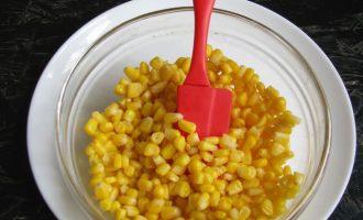 Открыть баночку с консервированной кукурузой, слить жидкость, а сами зерна высыпать в удобную посуде, для дальнейшего перемешивания. Часть кукурузы оставьте для украшения.