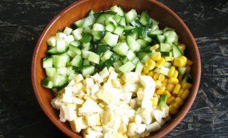 В миску с кукурузой присоедините нарезанные яйца и свежие огурчики.