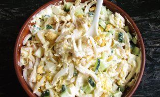 Все компоненты смешайте, чтобы все ингредиенты равномерно распределились в салате с кальмарами и свежим огурцом.