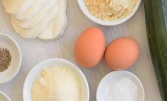 Подготовьте все компоненты для приготовления цукини с сыром в духовке. Вместо цукини можете взять кабачки. Также в этом рецепте потребуется два вида сыра, набор специй, пшеничная мука и свежие яйца. Заметьте, растительное масло и другие жиры отсутствуют.
