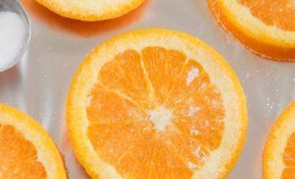 Включите духовой шкаф, установите температурный режим 180-200 С. Застелите противень алюминиевой фольгой. Каждый кружок апельсина обильно посыпьте сахаром и выложите на подготовленный противень.